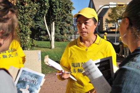 """""""汽车之旅""""负责人之一、来自埃德蒙顿的法轮功学员刘敏楠向到场记者讲法轮功被迫害真相。(黄钟乐/大纪元)"""
