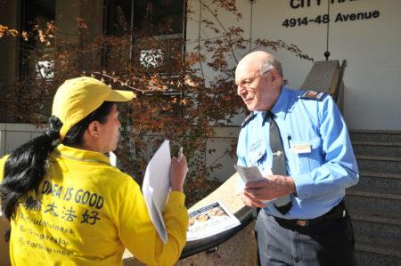 市政厅保安主动向法轮功学员索取更多真相资料帮助派发。(黄钟乐/大纪元)