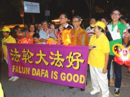 槟城第一副首席部长拿督莫哈末拉昔(横幅前排衣着长袖巴迪衫者)在主席郑锦泉等人陪同下,与民众和法轮功队伍一起提灯笼游行庆中秋。(大纪元)