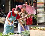 台风梅姬挟带丰沛雨量,造成农作损伤,农损超过新台币10亿元。图为民众趁台风天前到菜市场购买蔬菜。(陈柏州/大纪元)