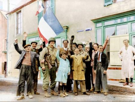 1944年6月12日,法国圣奥诺里讷镇的民众在三色旗下欢迎三名盟军(美国)大兵。(Courtesy of Marina Amaral)