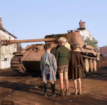 1944年8月25日,法国下诺曼底地区的法莱斯城,三个法国男孩看着一辆战败被弃的德国豹式坦克。(Courtesy of Marina Amaral)