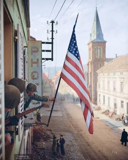 """法国东北部洛林的比奇镇,盟军第100步兵师第398步兵团第2营的托马斯格拉罕(Thomas H‧ Garahan)上尉举起当地法国姑娘偷偷做的""""星条旗""""。 (Courtesy of Marina Amaral)"""