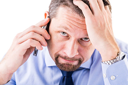 Stressed businessman making a phone call.(fotolia)