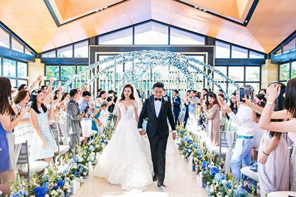 新郎新娘在婚礼红毯上,接受众亲友的祝福。(Lens婚礼影像机构提供)