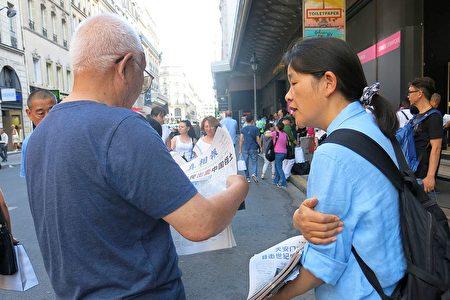 法轮功学员在向巴黎拉法耶特商店门前的大陆游客讲真相。(明慧网)