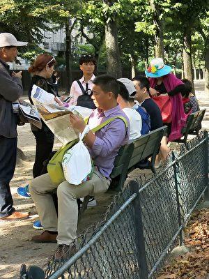 大陆游客在巴黎埃菲尔铁塔下休息时,认真阅读法轮功学员发送给他们的《真相报》。(明慧网)