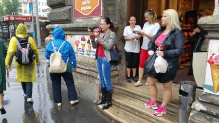 路边避雨的民众,忙着看真相资料、拍照。(大纪元)