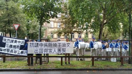 小帥哥前,「抗議中共阻撓王治文出國與家人團聚」的橫幅聲援王治文。(大紀元)