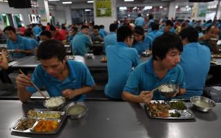 中國有很多35歲以上的男性移工,被迫下崗後很難再找到工作。圖為在東莞某鞋廠餐廳吃午餐的員工。(GREG BAKER/AFP/Getty Images)
