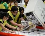 香港立法会选举经过马拉松式的点票,5日公布结果。图为票务人员将选票从票匦中倒出。(AFP)