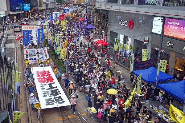 """十一前夕,亚洲有180万人连署举报中共前党魁江泽民。图为今年香港七一游行,民众高举""""法办江泽民""""的横幅。(潘在殊/大纪元)"""