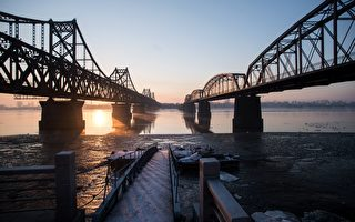 "The sun rises over the bridge on the banks of the Yalu River in the Chinese border town of Dandong opposite to the North Korean town of Sinuiju on February 9, 2016. The UN Security Council strongly condemned North Korea's rocket launch on February 7 and agreed to move quickly to impose new sanctions that will punish Pyongyang for ""these dangerous and serious violations."" AFP PHOTO / JOHANNES EISELE / AFP / JOHANNES EISELE        (Photo credit should read JOHANNES EISELE/AFP/Getty Images)"