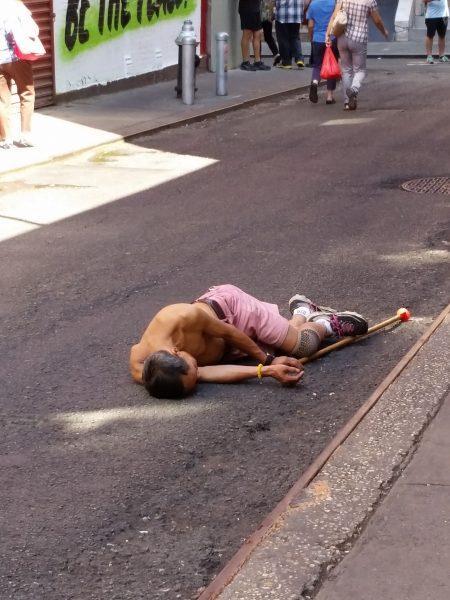 """这名中年人每天在华埠宰也街(Doyer Street)上,烦躁的走来走去,有时还会耍一下""""功夫"""",然后倒在街上睡觉/休息。 (陈家龄提供)"""