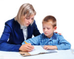 young boy learning to write under the supervision of the mother