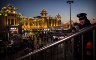 BEIJING, CHINA - FEBRUARY 17:  A Chinese security guard watches over passengers leaving for the Spring Festival at a local railway station on February 17, 2015 in Beijing, China. Millions of Chinese will travel home to visit families in a mass migration during the Spring Festival holiday period that begins with the Lunar New Year on February 19.  (Photo by Kevin Frayer/Getty Images)