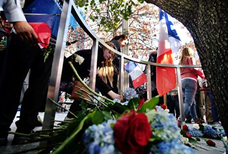People place flowers around the Survivor Tree at the 9/11 memorial in New York on November 16, 2015, to pay their respect for the victims of the Paris terrorist attacks. A series of coordinated attacks by gunmen and suicide bombers in Paris on November 13 that killed at least 129 people and injured 352 in scenes of carnage at a concert hall, restaurants and the national stadium. AFP PHOTO/JEWEL SAMAD (Photo credit should read JEWEL SAMAD/AFP/Getty Images)