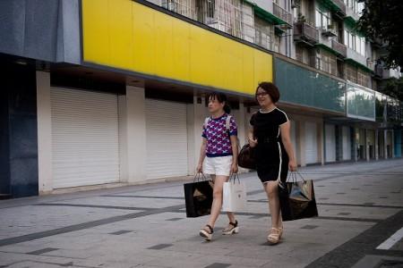 9月2日,两名女子经过几乎全部关闭的街道商店门前。(NICOLAS ASFOURI/AFP/Getty Images)