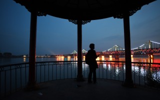 2016年9月11日,在朝鮮第五次核試驗之後,一名婦女從丹東眺望中朝友誼橋。    (GREG BAKER/AFP/Getty Images)