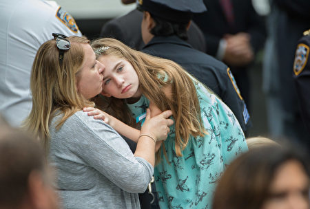 Family members embrace during the 15th Anniversary of September 11 at the 9/11 Memorial and Museum, on September 11, 2016 in New York. The United States on Sunday commemorated the 15th anniversary of the 9/11 attacks. / AFP / Bryan R. Smith (Photo credit should read BRYAN R. SMITH/AFP/Getty Images)