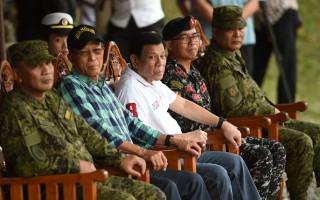 菲律賓總統杜特爾特(Rodrigo Duterte) (中,穿白衣者)發動鐵腕掃毒運動,在不到兩個月內殺掉近2千人。( TED ALJIBE/AFP/Getty Images)
