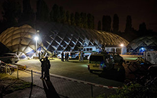 图为柏林Moabit区一个空气圆顶房屋的难民营,柏林警察正站在前面。   ( GREGOR FISCHER/AFP/Getty Images)