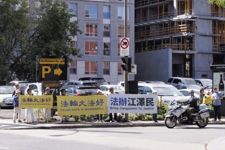 蒙特利尔法轮功学员在国际会展中心附近举着横幅传递讯息。(易柯 / 大纪元)