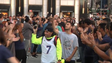 第一批拿到新iPhone的果粉兴奋地向围观的民众展示自己的手机。