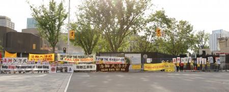 法轮功学员在酒店前,通过横幅向李克强一行传达讯息——停止迫害、法办江泽民。(梁耀/大纪元)