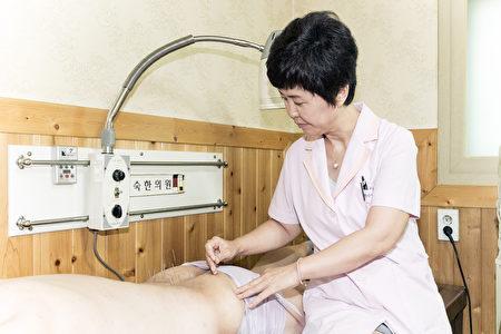 卢贤淑院长为患者针灸的场面。(全景林/大纪元)