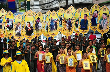 """This picture taken on September 17, 2016 shows people holding images of Thailand's King Bhumibol Adulyadej at a parade during the """"Khong Dee Muang Nara"""" (Good Products of Narathiwat) festival in Thailand's southern province of Narathiwat. / AFP / MADAREE TOHLALA (Photo credit should read MADAREE TOHLALA/AFP/Getty Images)"""