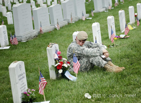 A soldier sits at a grave in Section 60 of Arlington National Cemetery May 25, 2009 in Arlington, Virginia. Section 60 is one of the main places where those who died while serving in the wars in Iraq and Afghanistan are buried. (Photo by Brendan Smialowski/Getty Images)