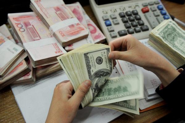 2016年10月12日,当局官方公布的人民币兑美元中间价报6.7258,创2010年9月14日来最低。(STR/AFP/Getty Images)