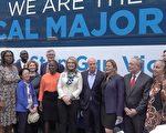 吉福德斯(前排中間穿黃衣的女士),和她的丈夫凱利(前排右5)在「聲音多數」巴士前與紐約民代官員合影。 (莊翊晨/大紀元)