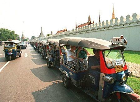 在路旁等候乘客的嘟嘟车。(Photo by PORNCHAI KITTIWONGSAKUL / AFP)