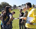 10月1日,一队外出游玩的年轻人在听闻真相后,主动向其他民众讲述活摘真相,并帮助法轮功学员征集签名。(周凤临/大纪元)