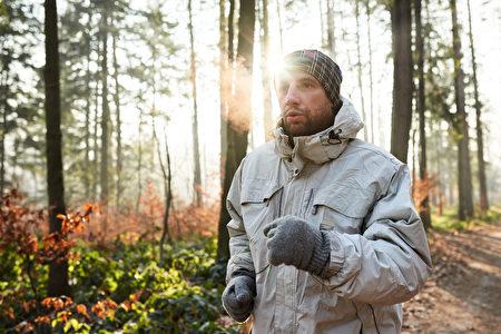 慢跑者穿着保暖衣物运行在森林冬季的一天