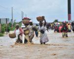 颶風馬修5日侵襲海地,大水淹沒道路,人們涉水而過。(HECTOR RETAMAL/AFP/Getty Images)