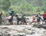 颶風馬修5日侵襲海地,造成橋樑崩塌,人們涉水渡拉迪格河。(HECTOR RETAMAL/AFP/Getty Images)
