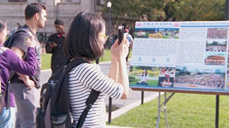 受到震撼的华人学生纷纷拿起手机拍摄图片内容。