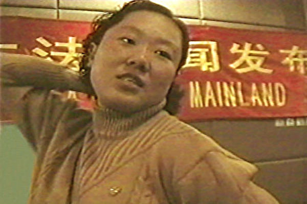 丁延在1999年10月28日北京新聞發布會上,向記者描述警察用背銬的酷刑折磨學員(明慧网)