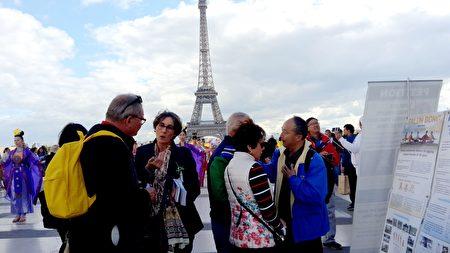 遊客在鐵塔前的人權廣場了解真相。(慈蕊/大紀元)