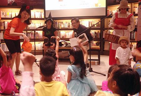 美國在台協會(AIT)處長梅健華(後右2)與夫人陳舲舲(後右3)在萬聖節即將來臨前,22日到一家書店為小朋友說故事,還一一發糖果,吸引大批小朋友與家長前往,他也直呼很開心。(中央社)