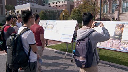 从大陆来的学生看到图片展都很震惊,纷纷拿出手机拍摄。