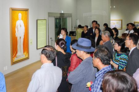 前来观看美展的各界人士在认真听解说员讲解每幅画的含意。(韩国记者站/大纪元)