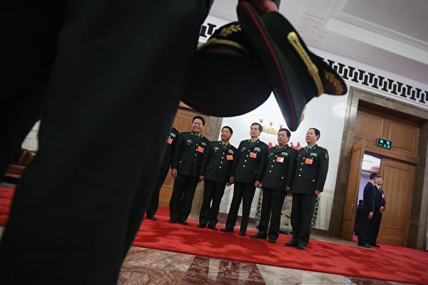 BEIJING, CHINA - MARCH 15: Delegates from Chinese People's Liberation Army take photos at the entrance of the meeting room for the fifth plenary meeting of the National People's Congress at the Great Hall of the People on March 15, 2013 in Beijing, China. Li Keqiang was elected as China's Premier Friday at the 12th National People's Congress, the country's top legislature. (Photo by Feng Li/Getty Images)