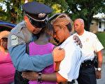 2015年8月20美國弗格森,一名警員與當地居民在紀念一名為誤傷的非裔兒童活動中。 (Michael B. Thomas/ Getty Images)