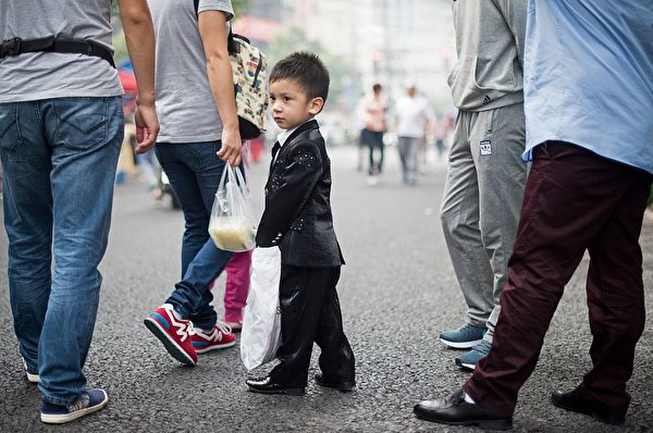 A Chinese Muslim boy, clad in new clothes for the sacrificial Eid al-Adha festival, is seen on a street in Shanghai on September 24, 2015.  Muslims across the world celebrate the annual festival of Eid al-Adha, or the Festival of Sacrifice, which marks the end of the Hajj pilgrimage to Mecca and in commemoration of Prophet Abraham's readiness to sacrifice his son to show obedience to God.   AFP PHOTO / JOHANNES EISELE        (Photo credit should read JOHANNES EISELE/AFP/Getty Images)