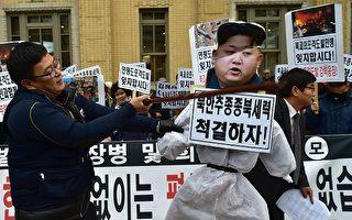 在抗議人群中,一名韓國人士用木棒打擊金正恩的紙肖像。( JUNG YEON-JE/AFP/Getty Images)