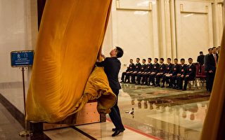 A man pulls curtains near Chinese paramilitary guards in the Great Hall of the People during the opening ceremony of the National People's Congress in Beijing on March 5, 2016. Chinas Communist-controlled parliament opened its annual session on March 5 and is expected to approve a new five-year plan to tackle slowing growth in the worlds second-largest economy.  / AFP / FRED DUFOUR        (Photo credit should read FRED DUFOUR/AFP/Getty Images)